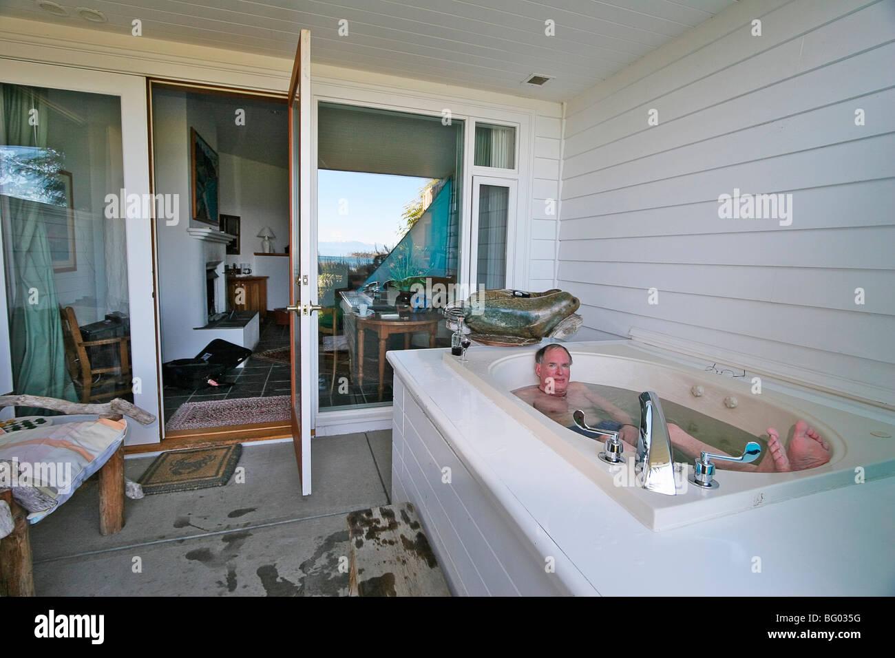El hombre disfruta de la tina caliente con un vaso de vino de oporto justo fuera de su Sooke Harbour House las habitaciones Imagen De Stock
