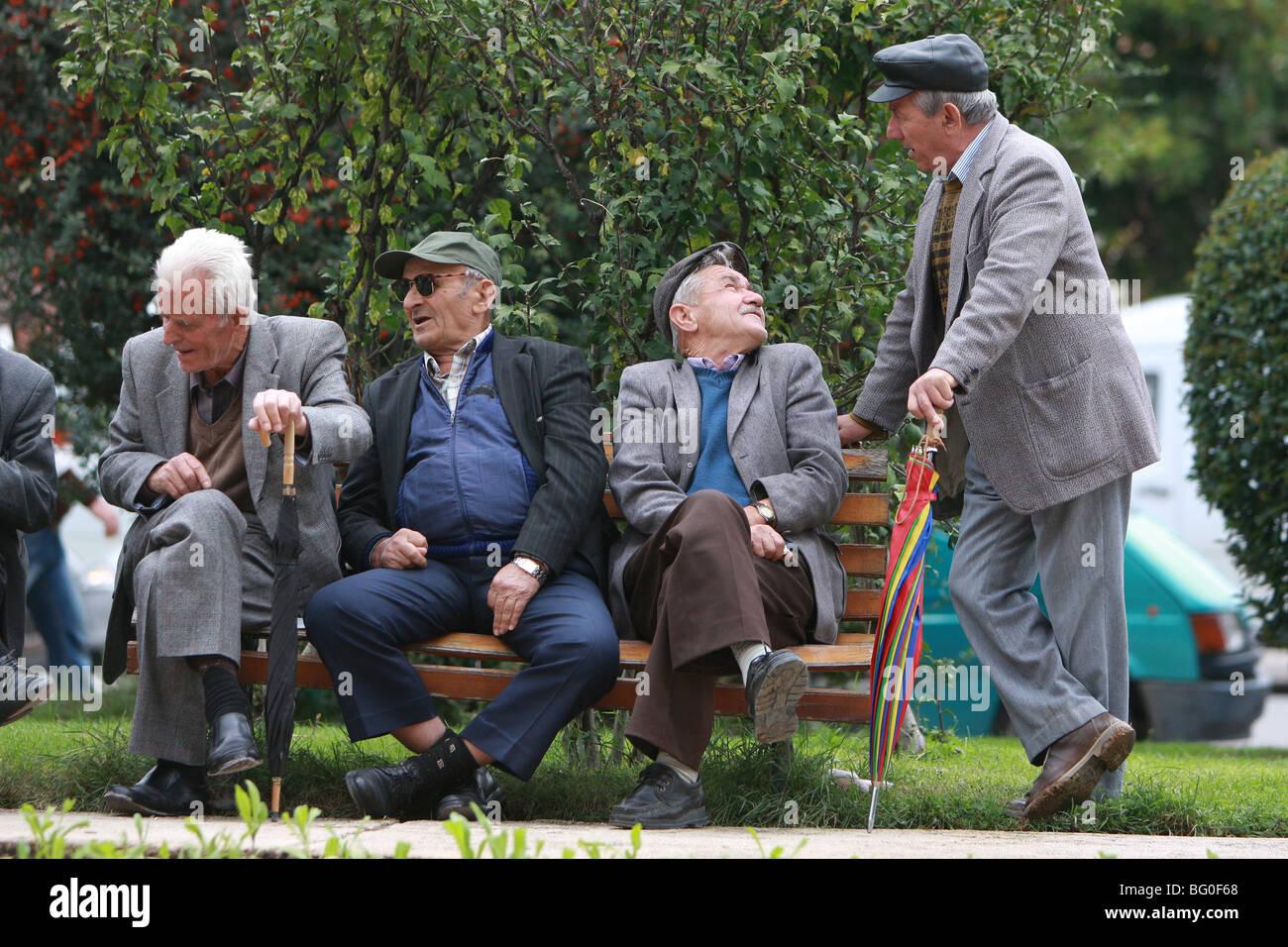 Un grupo de antiguos hombres hablando en un parque en Tirana, Albania Imagen De Stock