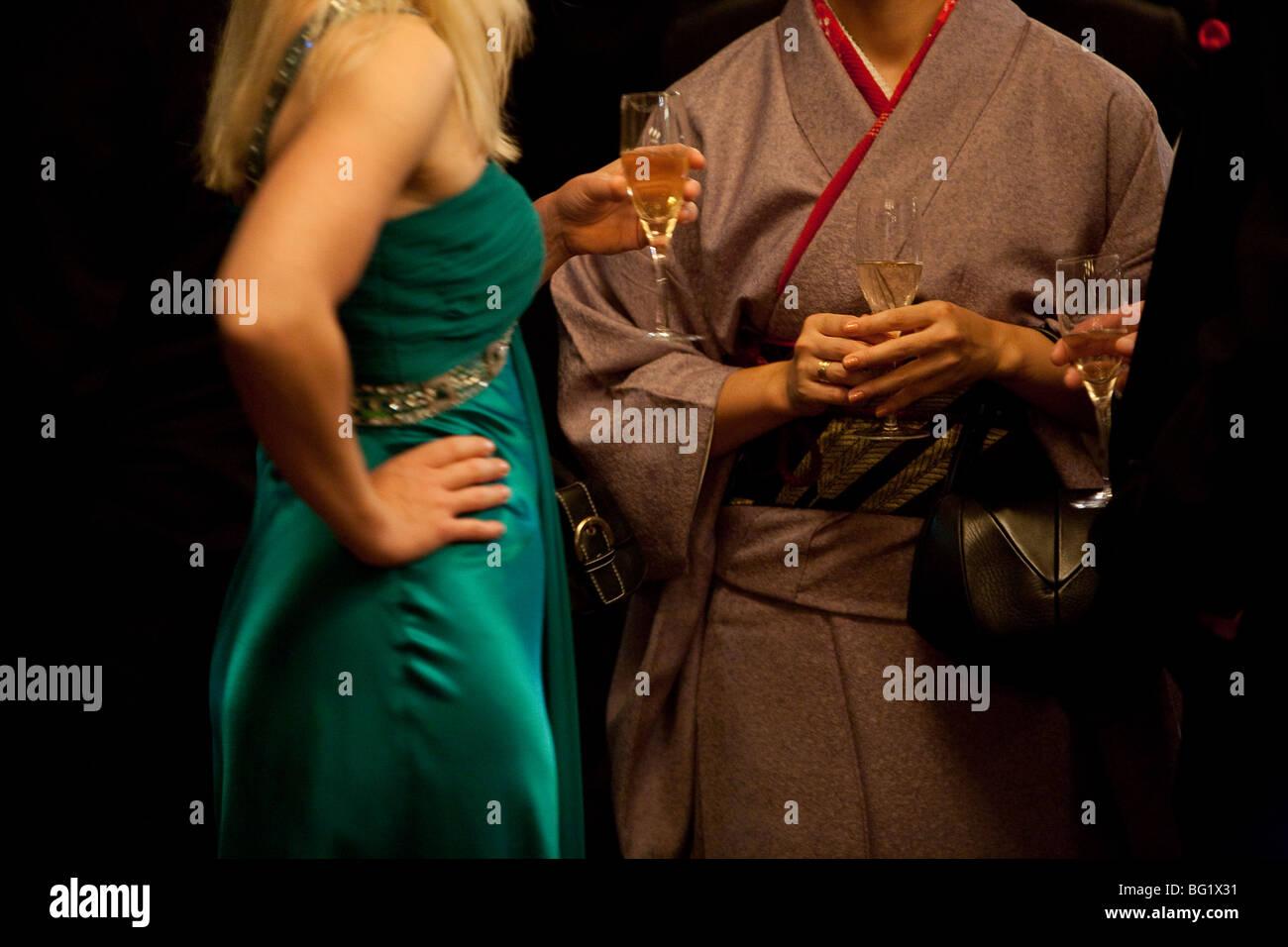 Mujer japonesa en kimono bebiendo champán con mujer en vestidos al estilo occidental. Imagen De Stock