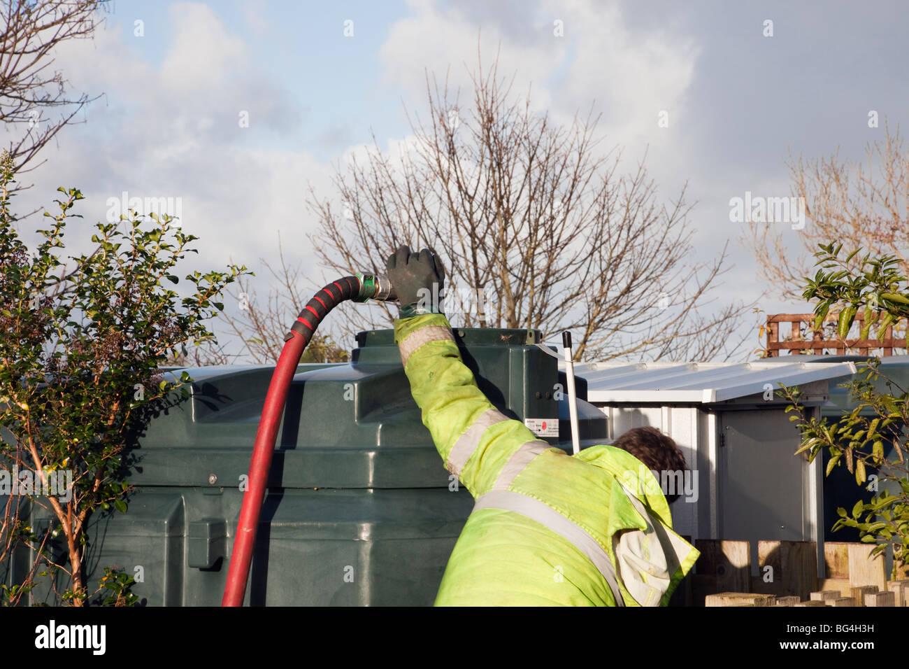 Hombre llenando un depósito de aceite doméstico con rojo y la boquilla del tubo de alimentación. Imagen De Stock