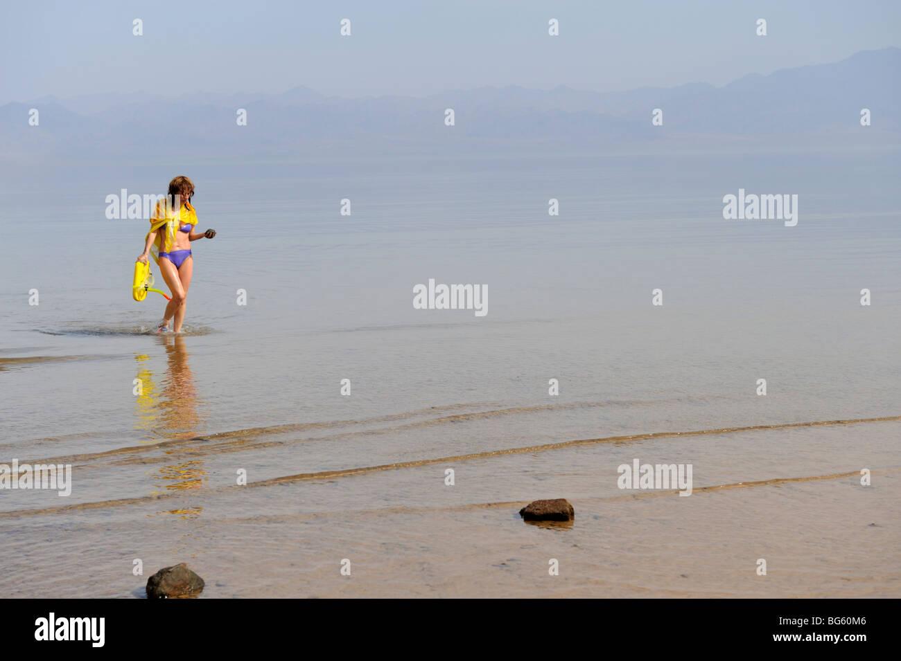 Mujer en bikini saliendo del mar con atmósfera brumosa Imagen De Stock
