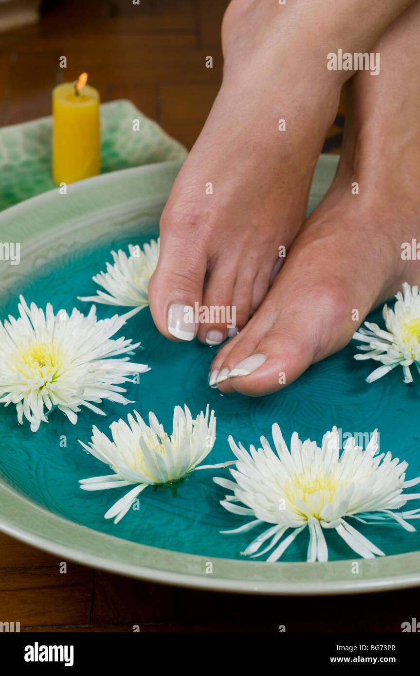 Pies disfrute de un relajante remojo de pies de aromaterapia en el spa de día Imagen De Stock