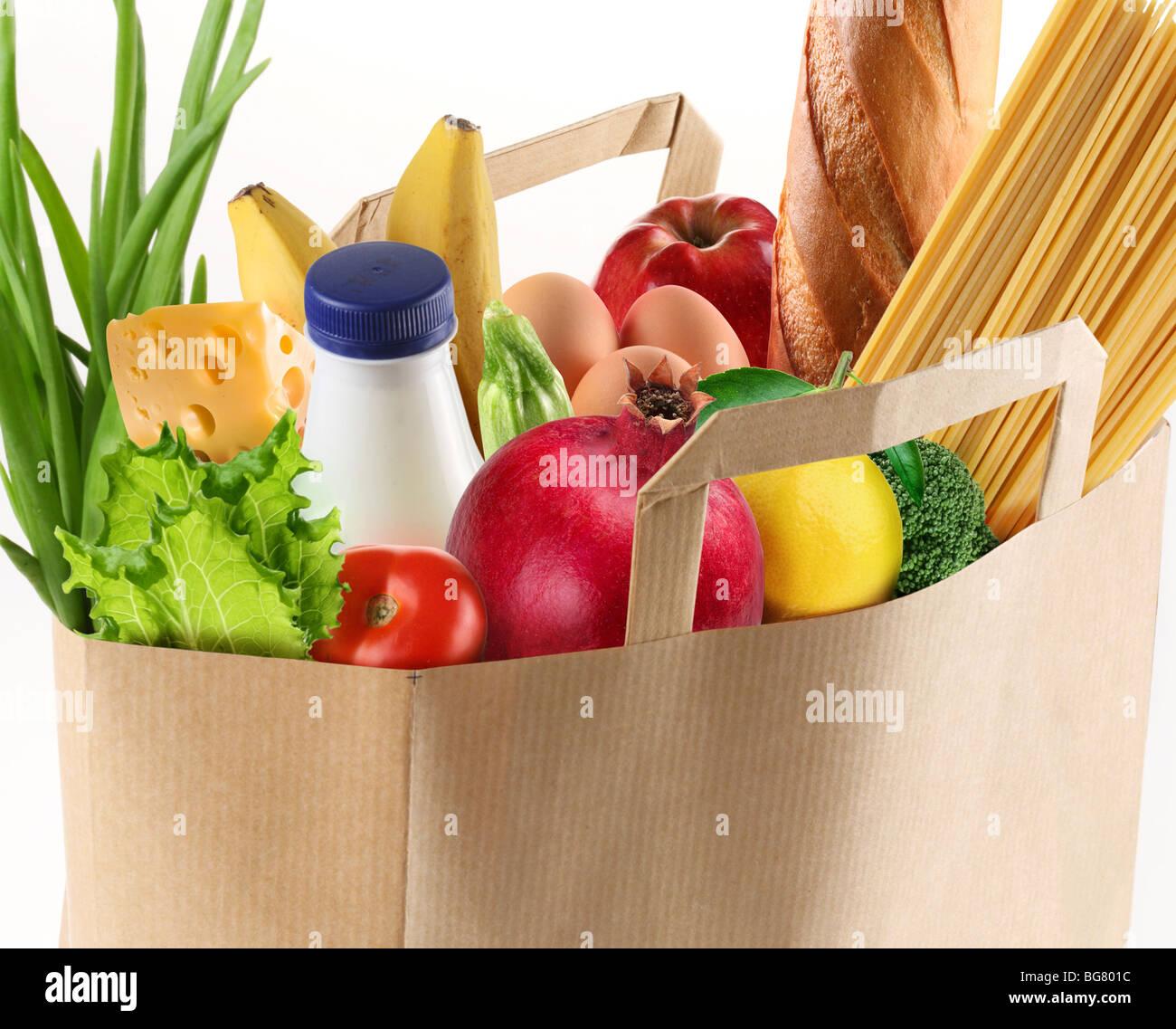 Bolsa de papel con la comida sobre un fondo blanco. Imagen De Stock