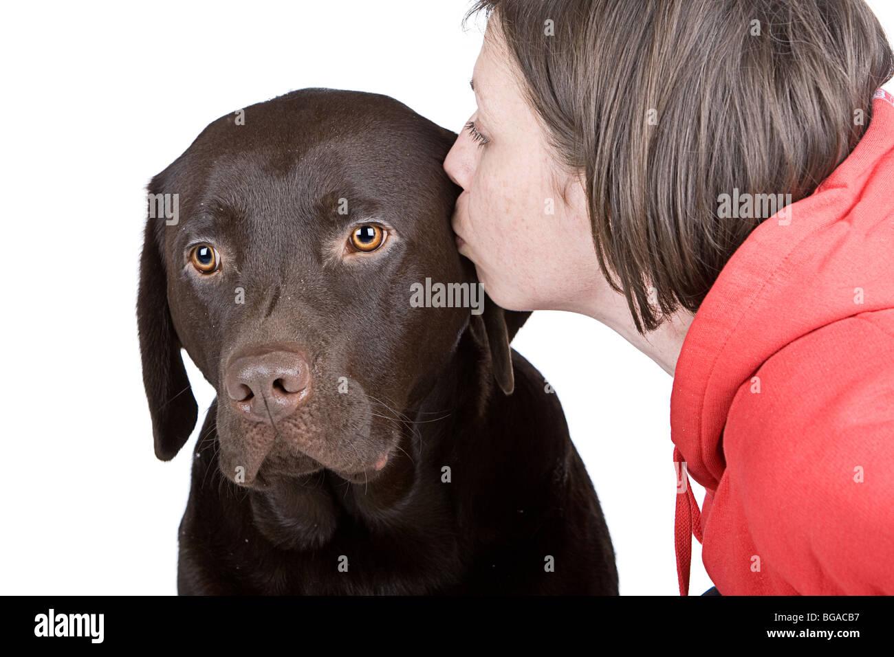 Disparo de un 30S Hembra besando a su mascota Labrador Chocolate Foto de stock