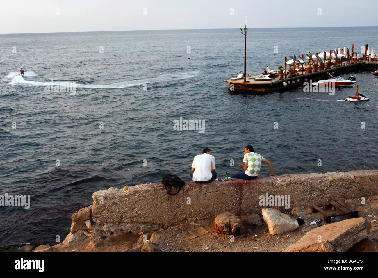Dos hombres se sientan a lo largo de la orilla del mar, cerca del paseo marítimo Cornich en Beirut en el Líbano. Imagen De Stock