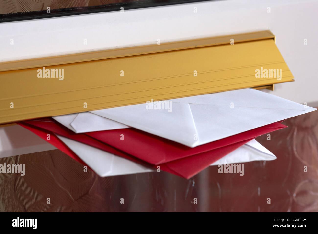 Cartas y tarjetas postales en el buzón de una casa en el reino unido Imagen De Stock