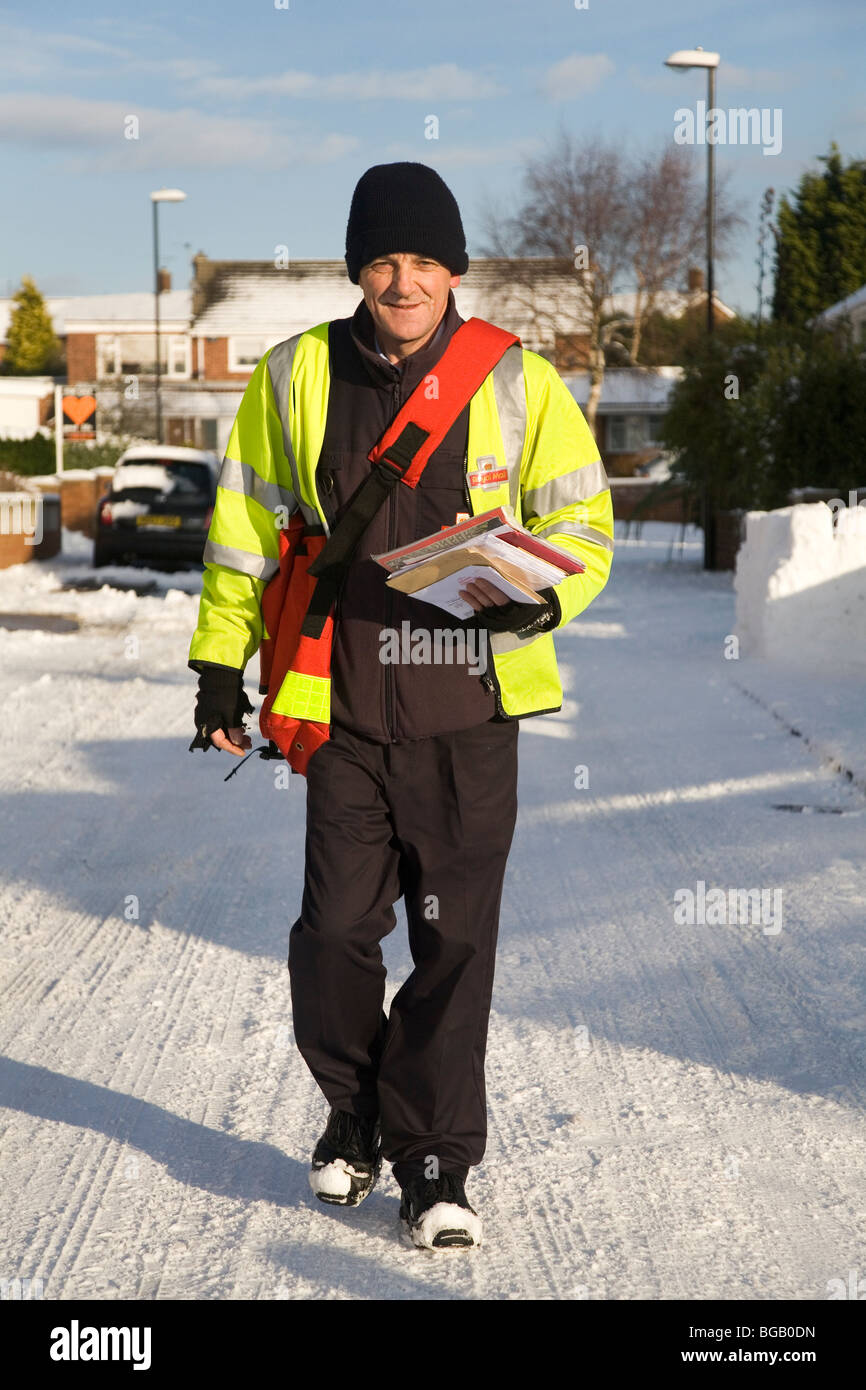 Un cartero hace sus entregas de Navidad a pesar de la nieve que ha afectado a las condiciones de la carretera en Imagen De Stock