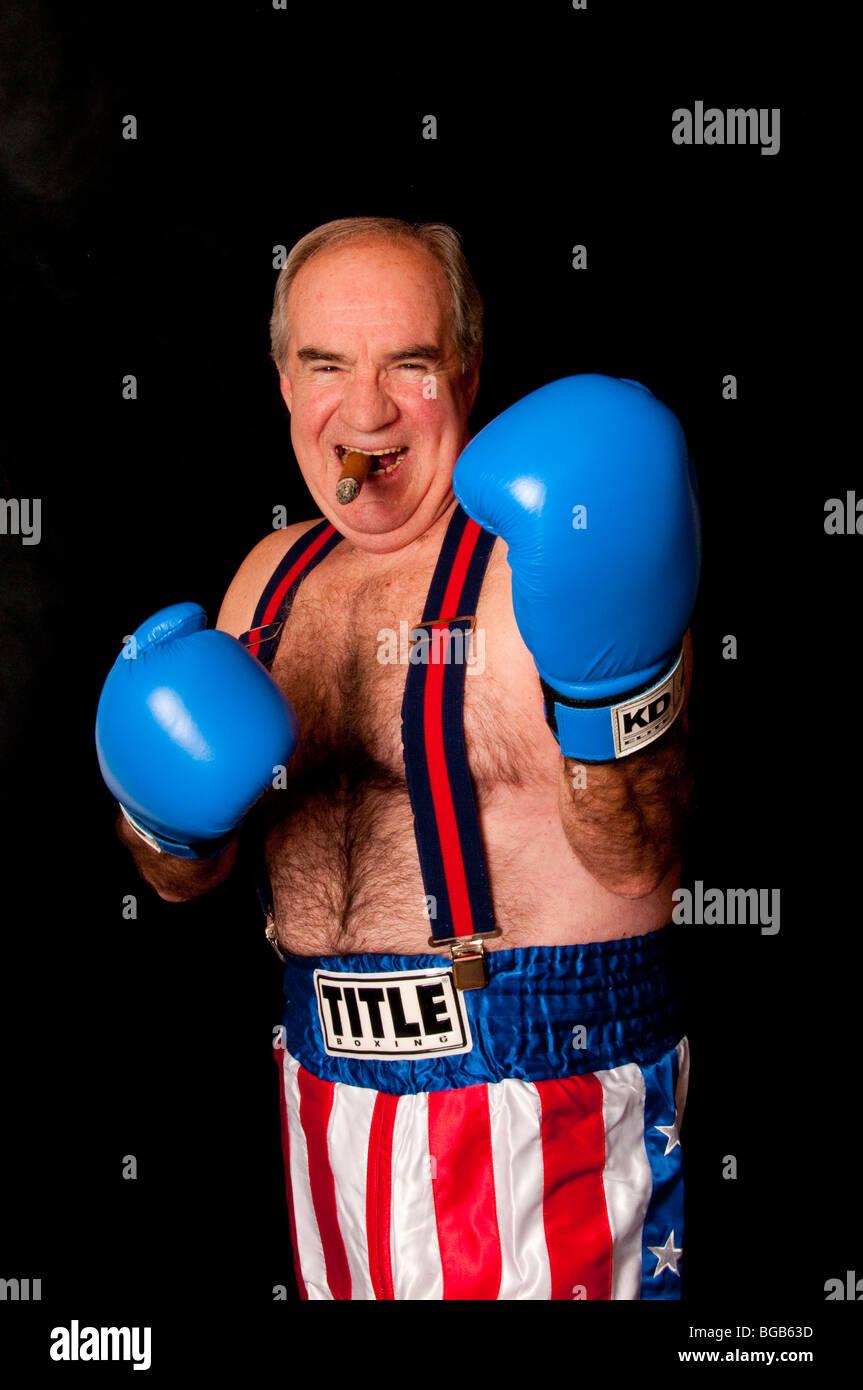 Envejecimiento boxer sobre fondo negro con bandera americana boxer troncos, guantes azules y tirantes fumar un cigarro Foto de stock