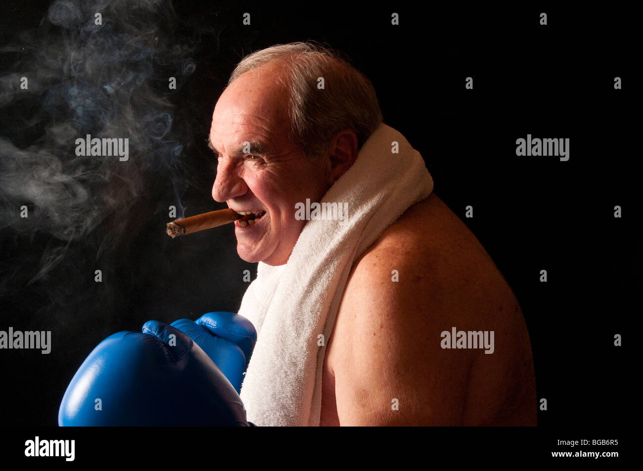 Perfil de envejecimiento boxer con cigarro y la sonrisa en la cara. Toalla alrededor de cuello azul con guantes de boxeo en posición de combate. Foto de stock