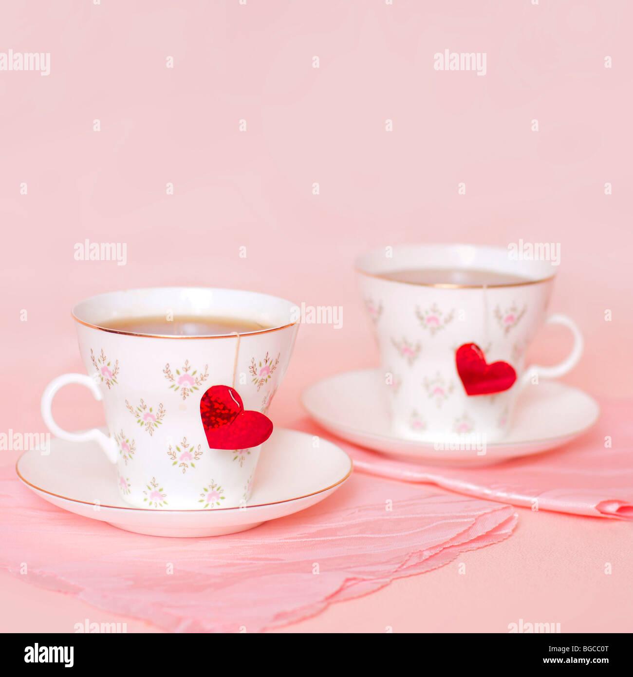 Dos tazas con corazones en el fondo de color rosa Foto de stock