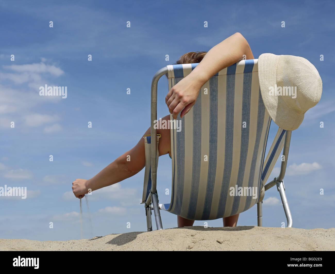 Mujer de relax en la playa en hamaca jugando con arena Imagen De Stock