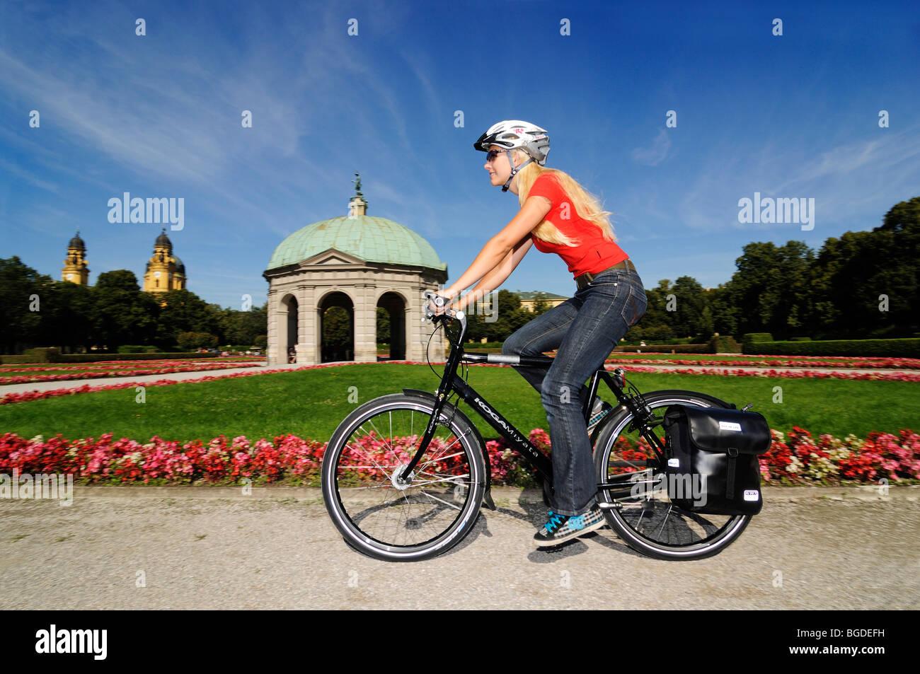 Mujer joven montar bicicleta, Hofgarten, Jardín, Munich, Baviera, Alemania, Europa Foto de stock