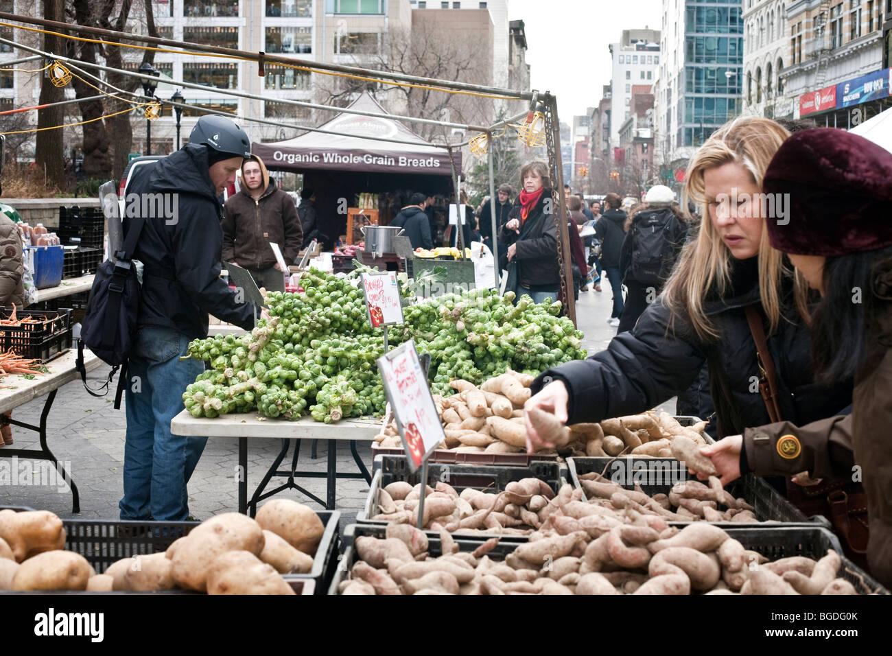 Los compradores consideran Selección de verduras en frío día bajo el cielo nublado en invierno los agricultores Foto de stock