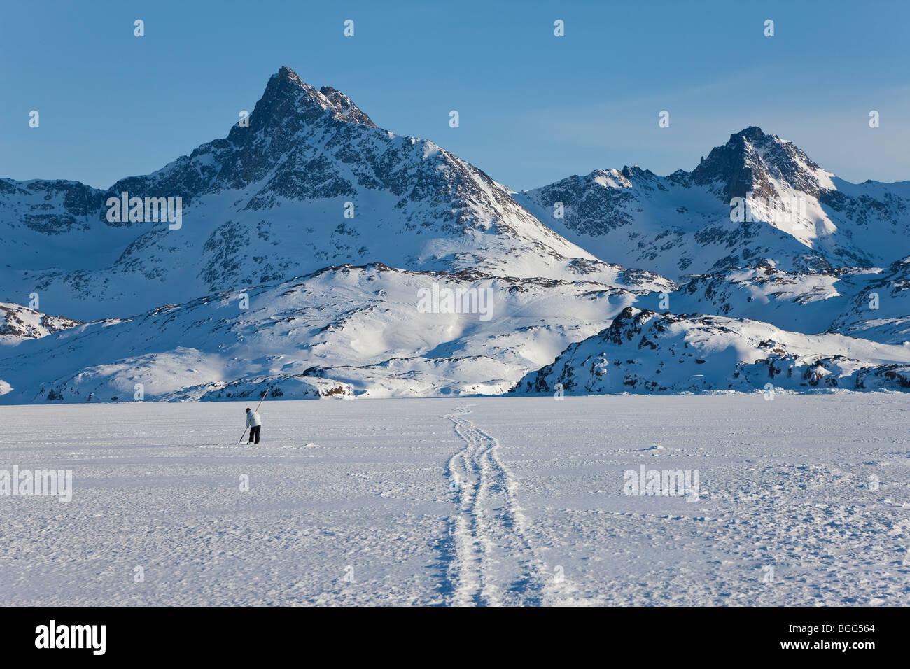 Pesca en el hielo, el rey Oscar Fijord, Tasiilaq, Groenlandia, el invierno Imagen De Stock