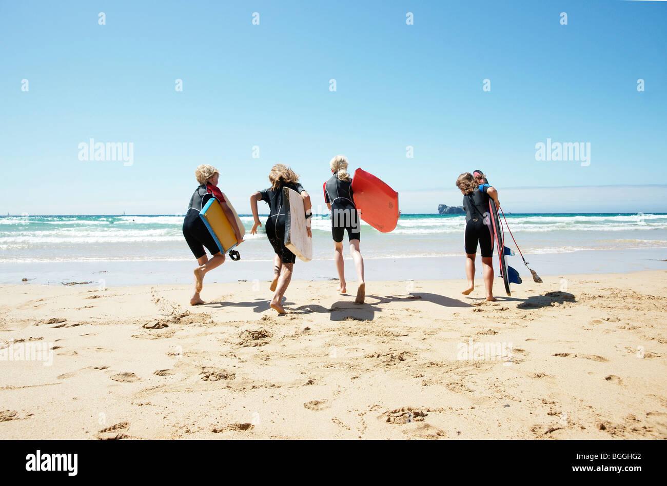 Los niños con tablas de surf en el agua, vista trasera Imagen De Stock
