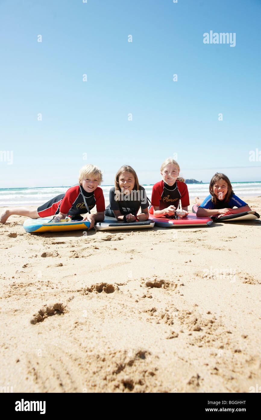 Los niños acostado con tablas de surf en la playa, vista frontal Imagen De Stock