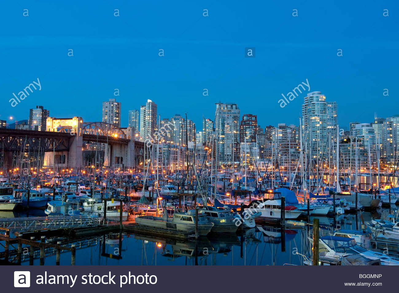 Un pequeño puerto boat en False Creek y el Vancouver skyline en penumbra, Vancouver, British Columbia, Canadá Imagen De Stock