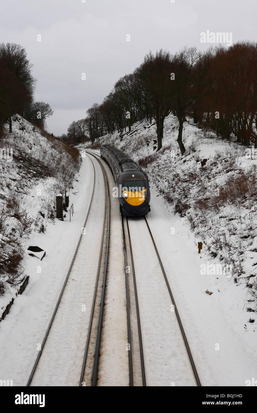 Un tren de alta velocidad Hitachi Javelin corriendo a través de la campiña de Kent nevado invierno en Inglaterra Foto de stock