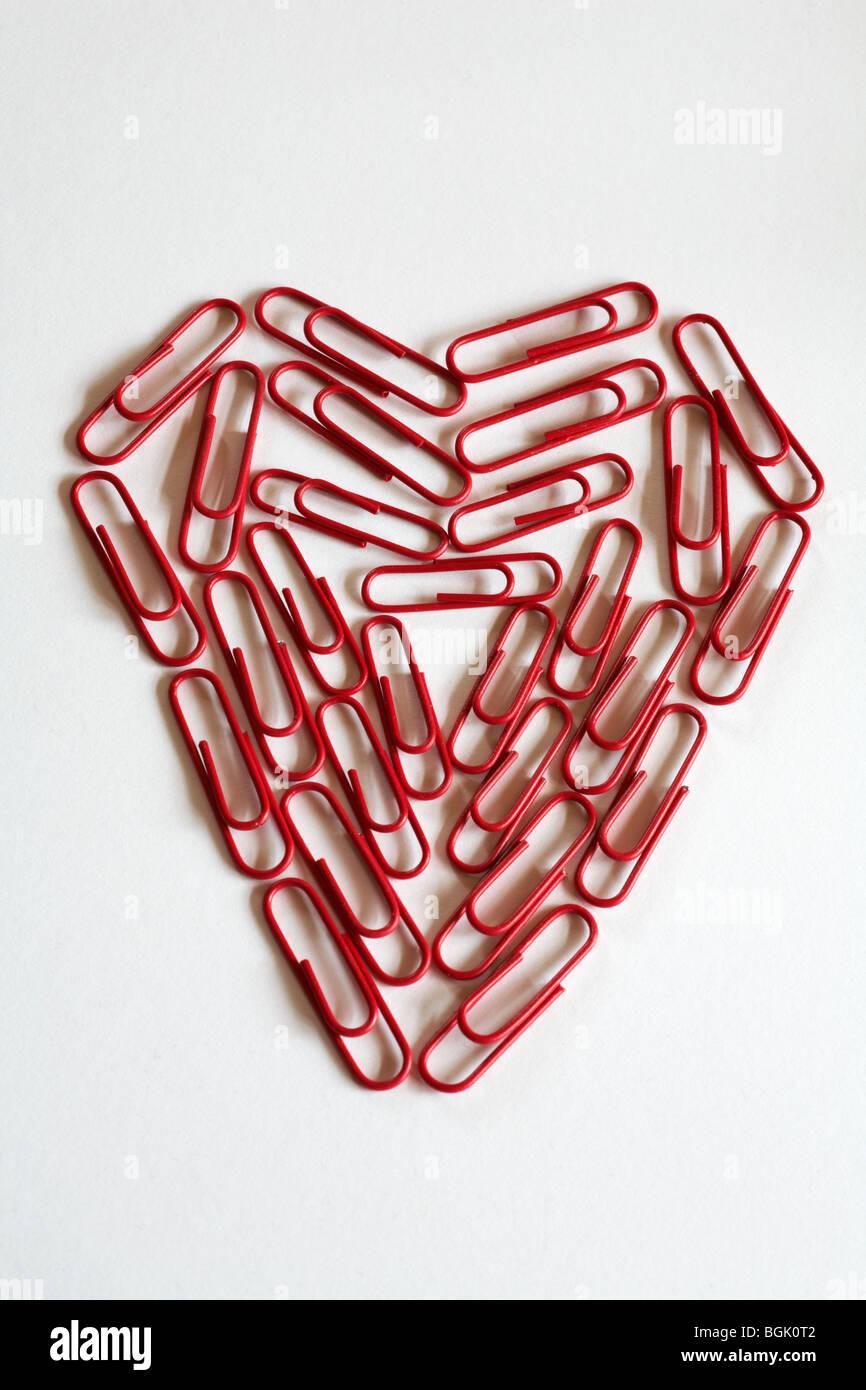 Concepto de romance de oficina - Corazón de papel rojo pinzas, clips, aislado sobre fondo blanco. Foto de stock