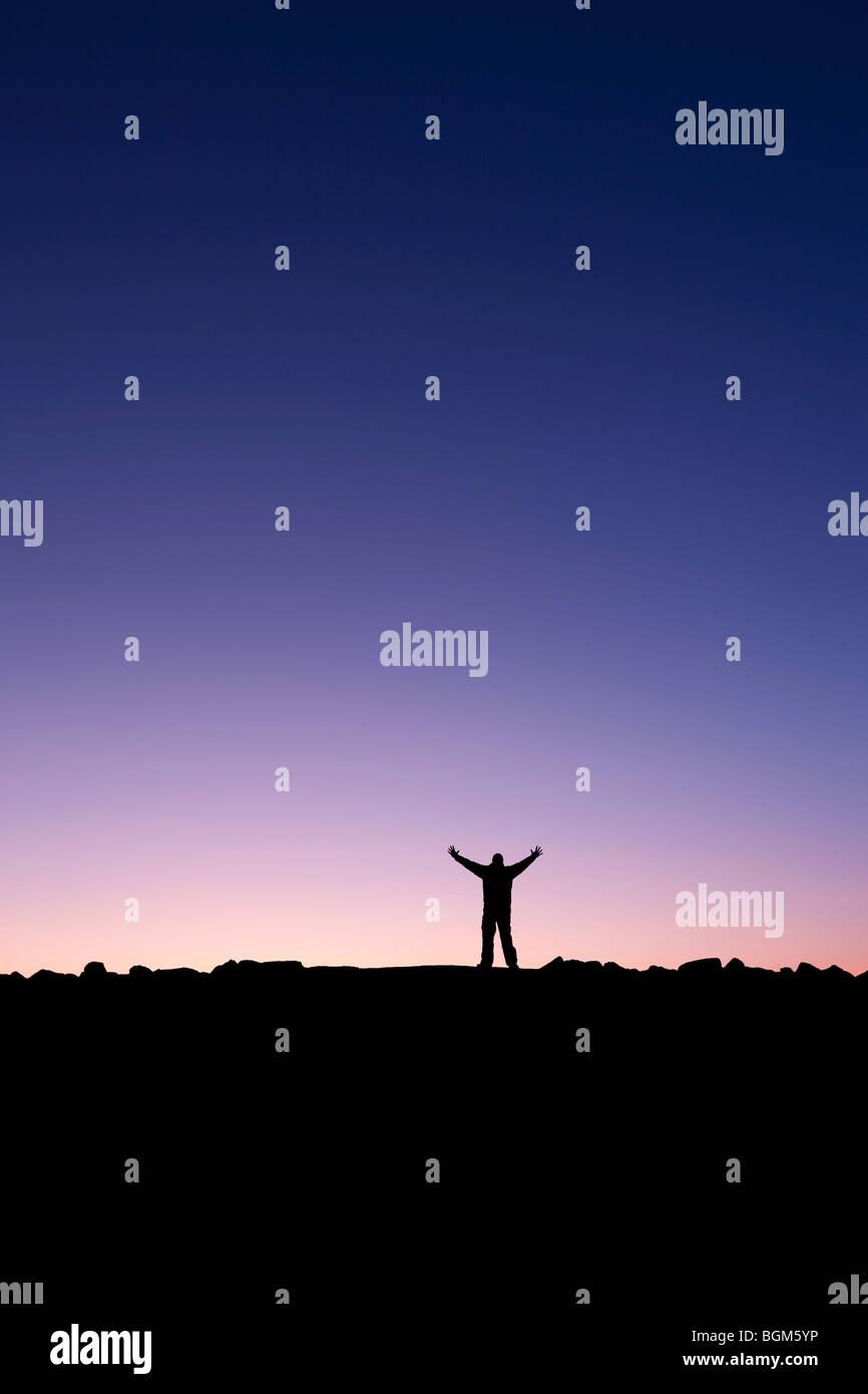 Silueta de un hombre levantando sus manos en el amanecer después de conquistar una cumbre Imagen De Stock