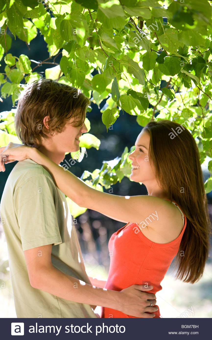 Una joven pareja abrazada bajo un árbol Imagen De Stock