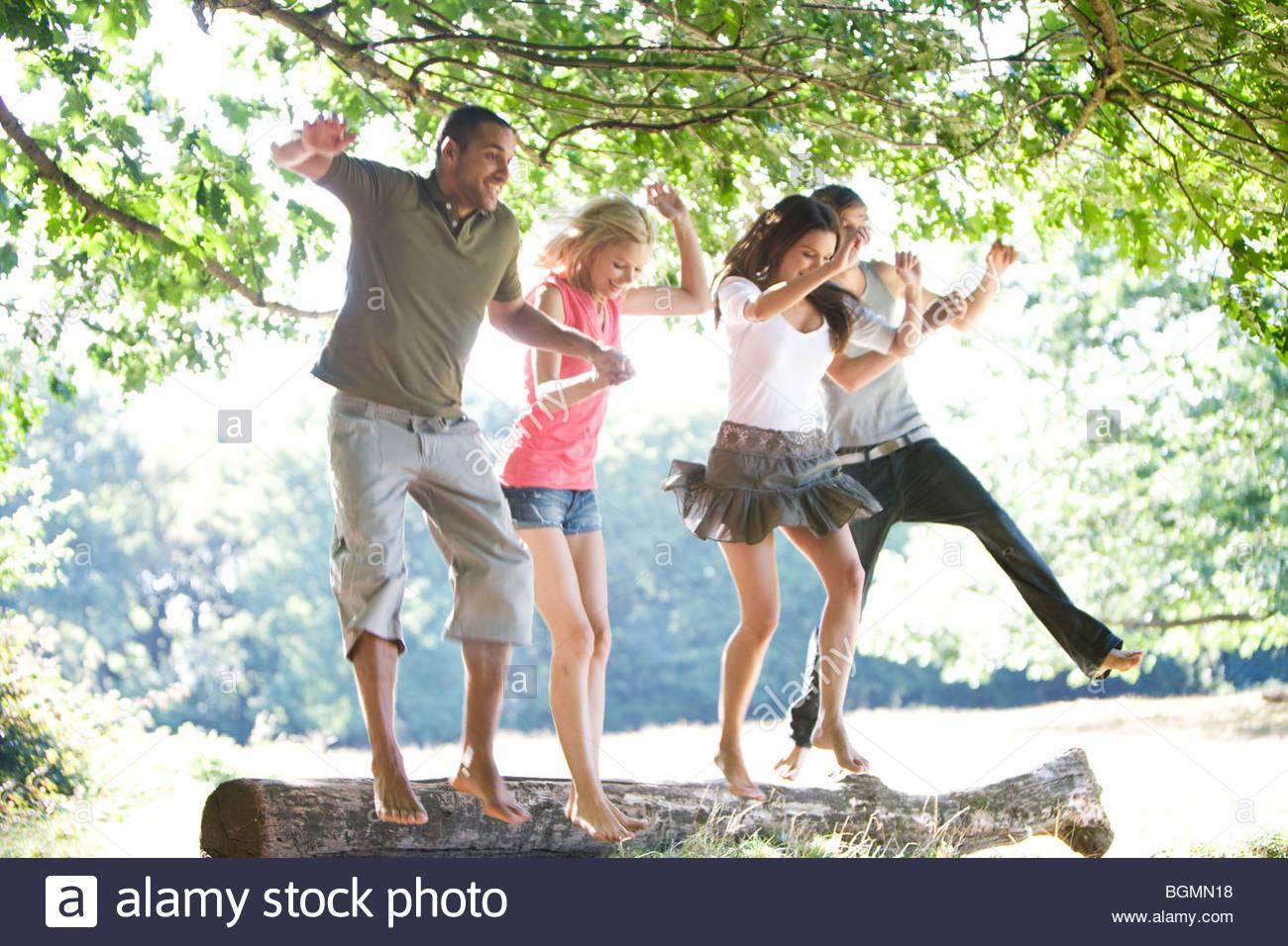 Cuatro jóvenes saltando desde un registro Imagen De Stock