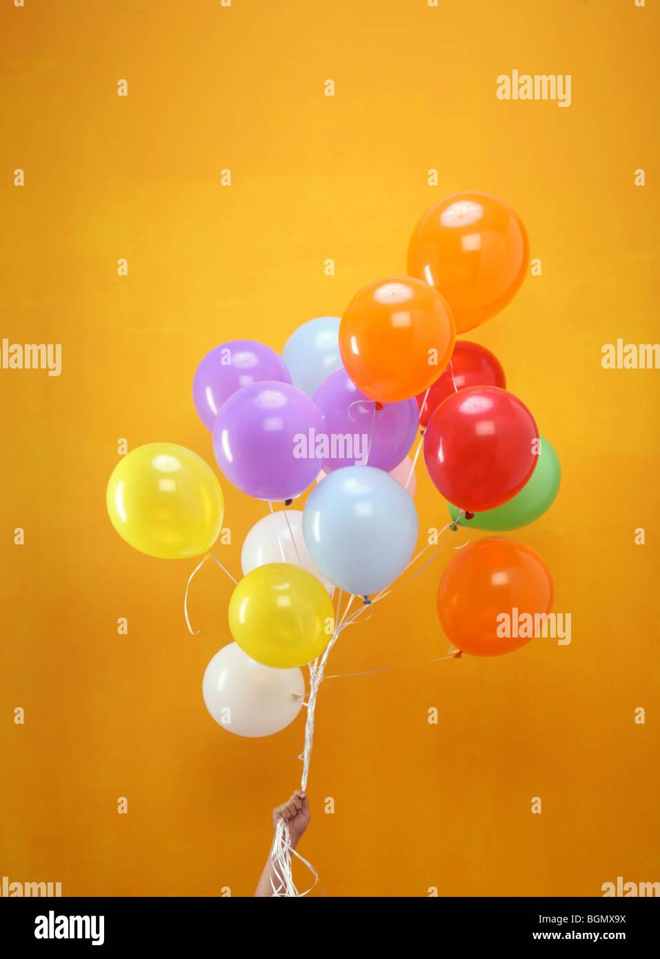 Globos de colores en un grupo organizado por una mano con fondo naranja Imagen De Stock