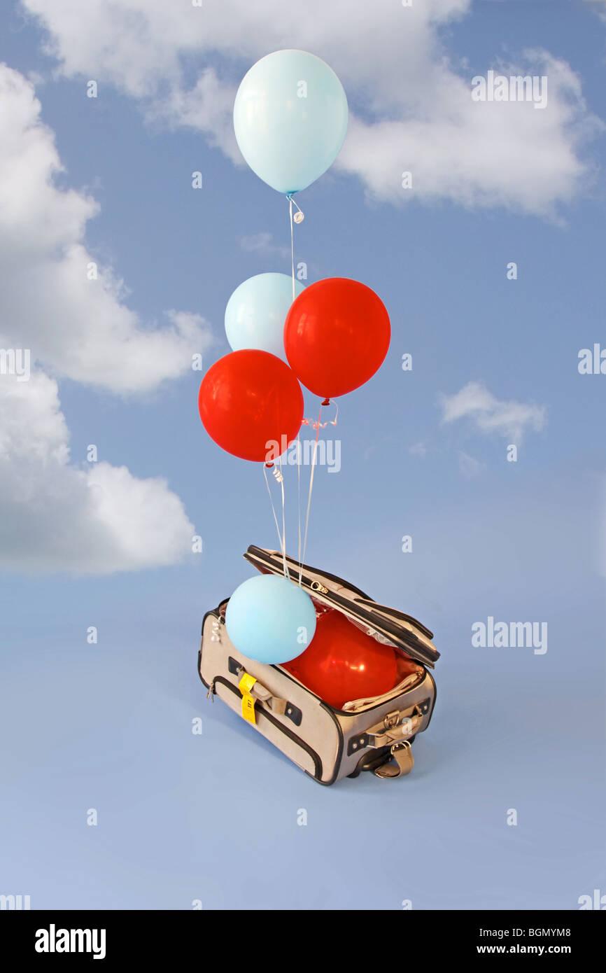 Los globos se elevan desde maleta abierta Imagen De Stock