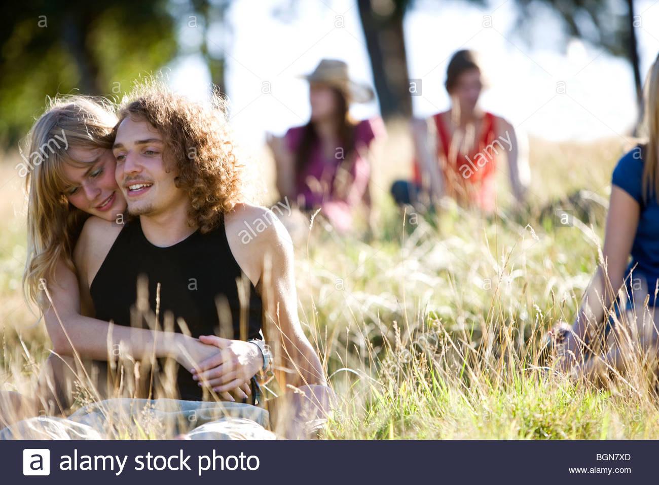 Una joven pareja sentada en un parque abrazando, jóvenes en el fondo Foto de stock