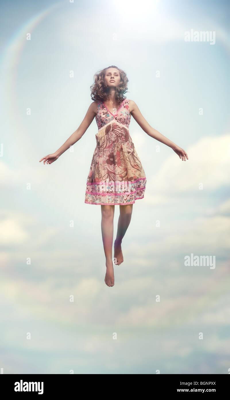 Mujer joven volando hacia arriba. Colores suaves. Imagen De Stock
