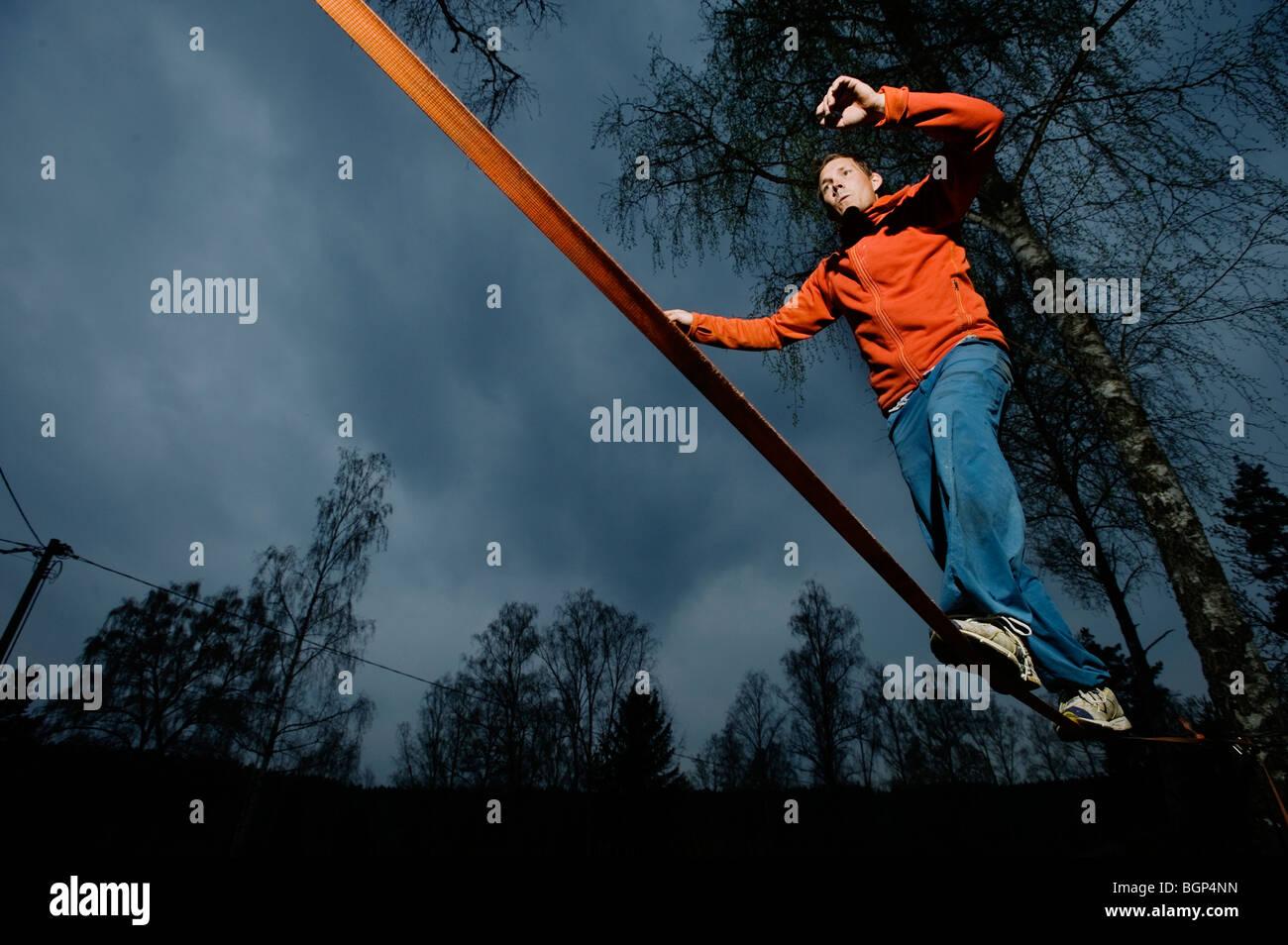 Un hombre equilibrio sobre una cuerda. Imagen De Stock