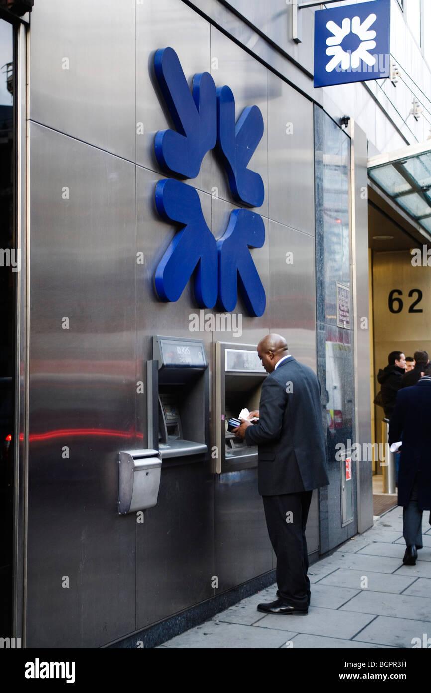 Hombre retirar dinero de los cajeros automáticos, en Londres, Inglaterra, Gran Bretaña, REINO UNIDO Imagen De Stock