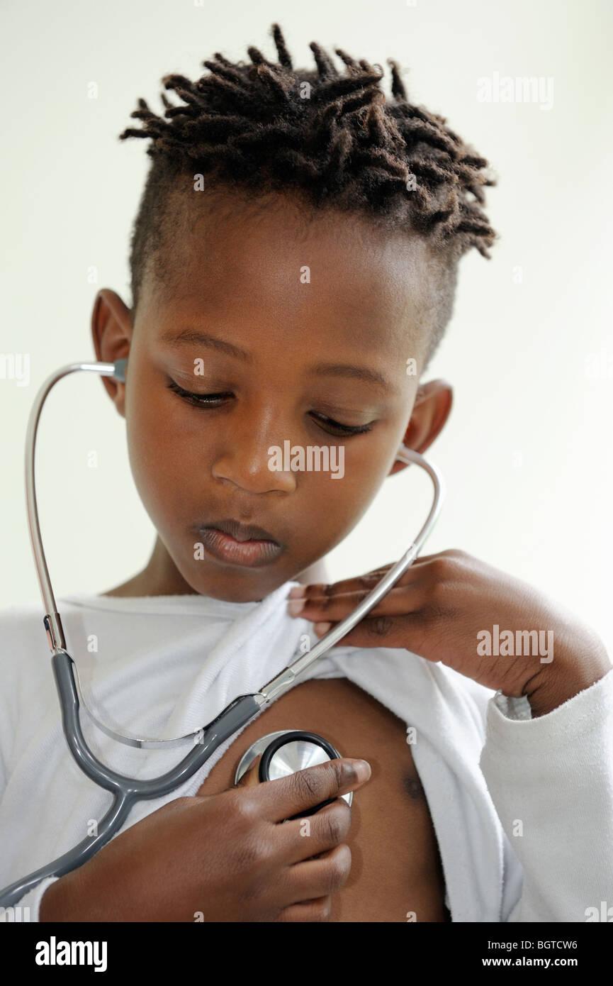 Chico escucha propios latidos con estetoscopio, Ciudad del Cabo, Western Cape, Sudáfrica Imagen De Stock
