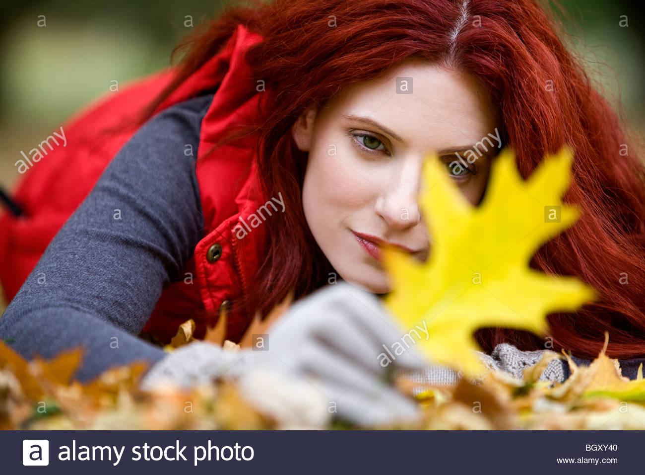 Una joven mujer tendida en el suelo, en busca de una hoja de otoño Foto de stock