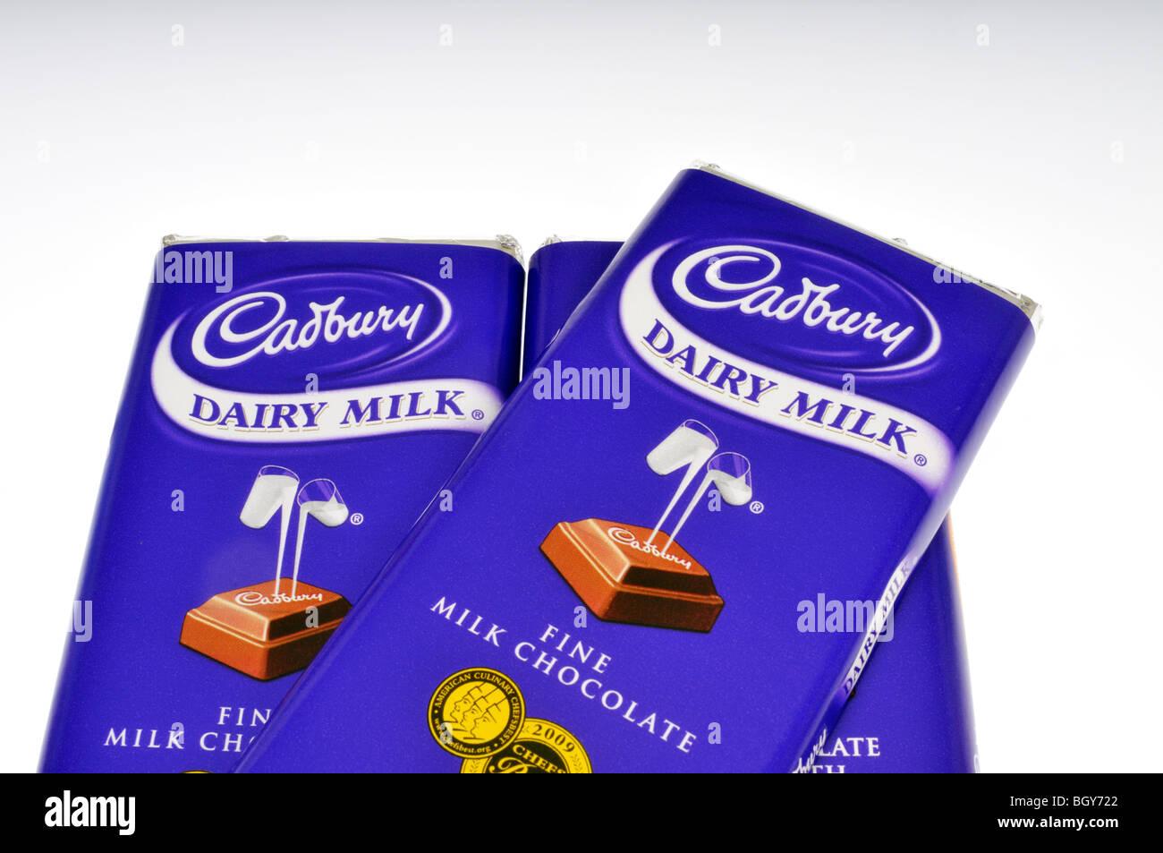 3 barras de caramelo de chocolate Cadbury en contenedores sobre fondo blanco. Foto de stock