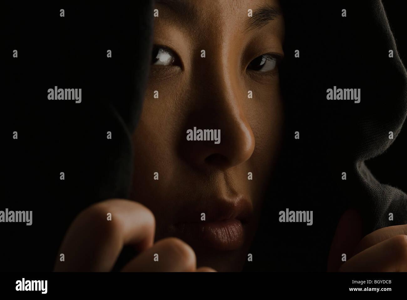 Mujer tirando bordes de cierre del capó, oscureciendo cara Imagen De Stock