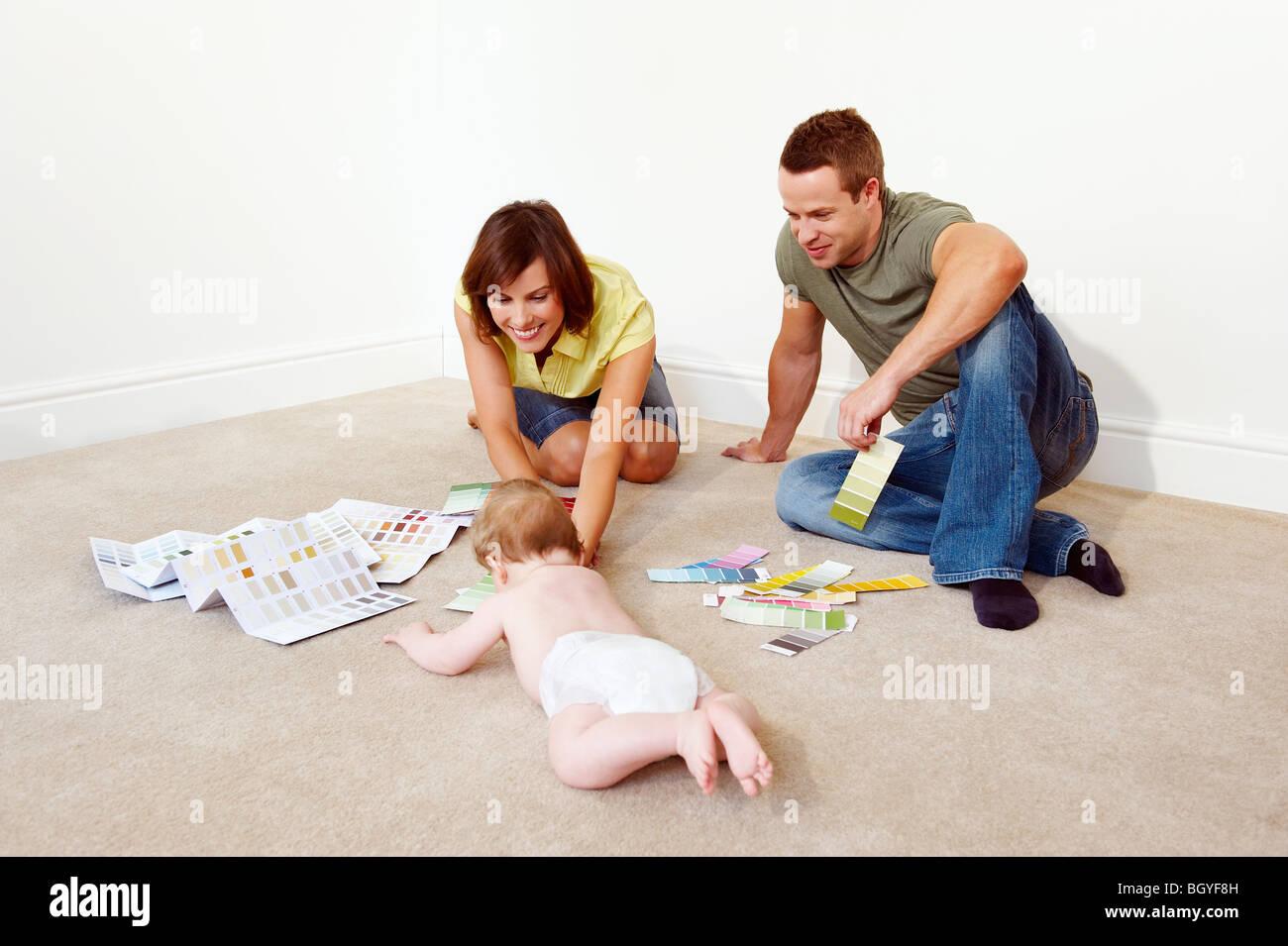 Familia joven en el piso con las muestras de color Imagen De Stock