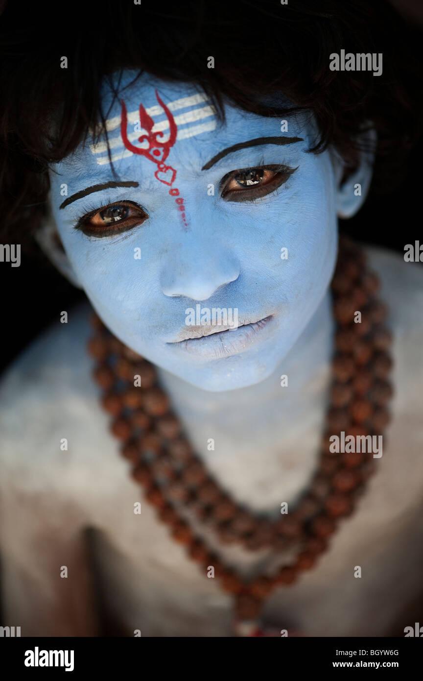 Niño Indio, la cara pintada, como el dios Hindú Shiva contra un fondo negro. La India Imagen De Stock