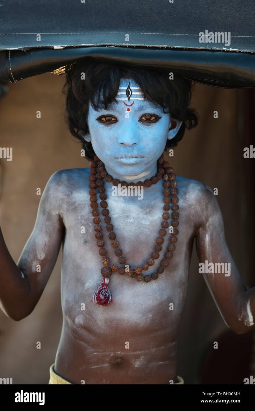 Niño Indio, la cara pintada, como el dios Hindú Shiva de pie en un rickshaw. En Andhra Pradesh, India Imagen De Stock