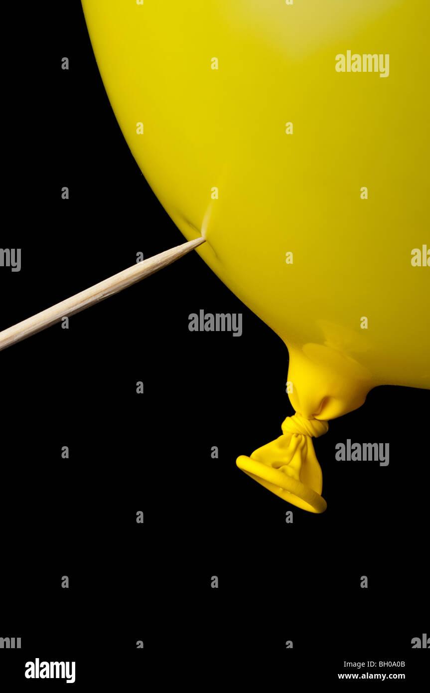 Un palo puntiagudo listo para pop en un globo amarillo sobre negro Imagen De Stock