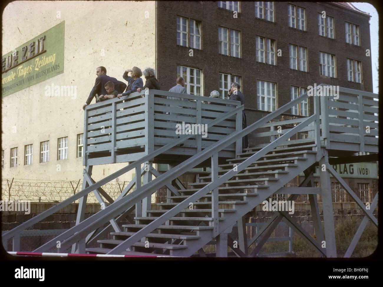Los turistas que buscan en Alemania Oriental. Berlín, junto al Muro de Berlín, visto desde Alemania Occidental Imagen De Stock