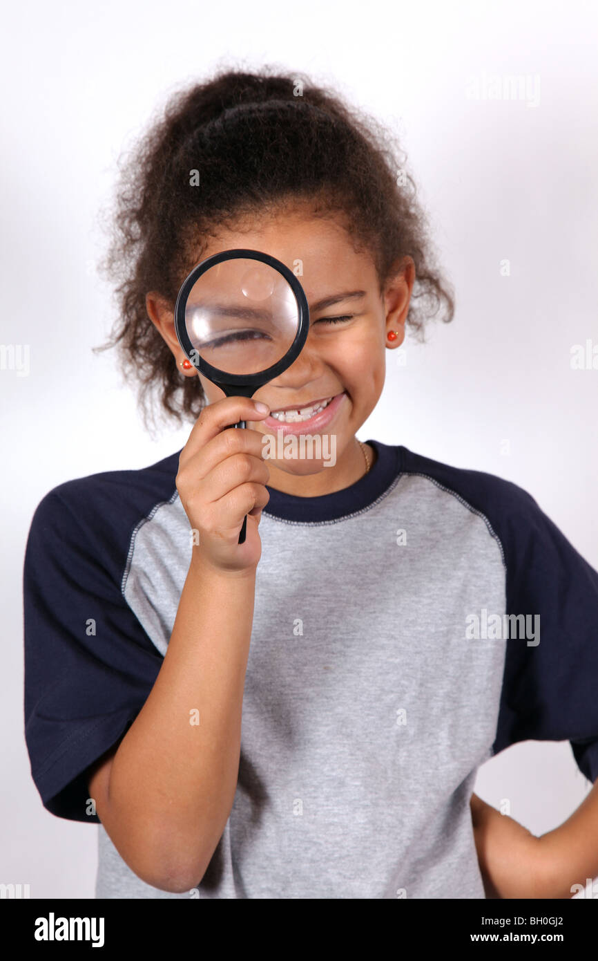 Chica afroamericana mirando a través de una lupa Imagen De Stock