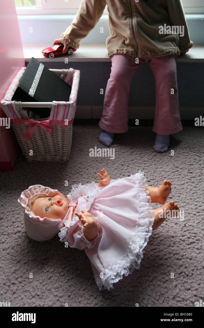 Una niña juega con un coche de juguete junto a una muñeca desechados. Imagen De Stock