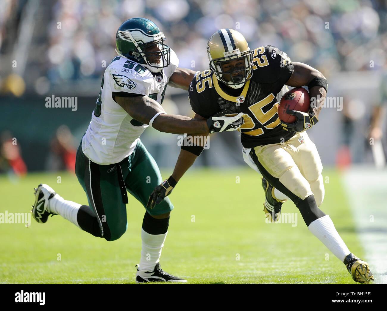 Reggie Bush #25 de los New Orleans Saints corre con el balón como Akeem Jordan #56 de los Philadelphia Eagles Imagen De Stock