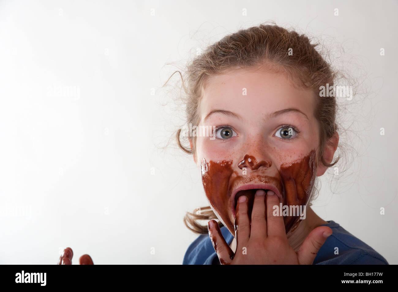 Niña sonriendo a través de cara cubiertas de chocolate Imagen De Stock