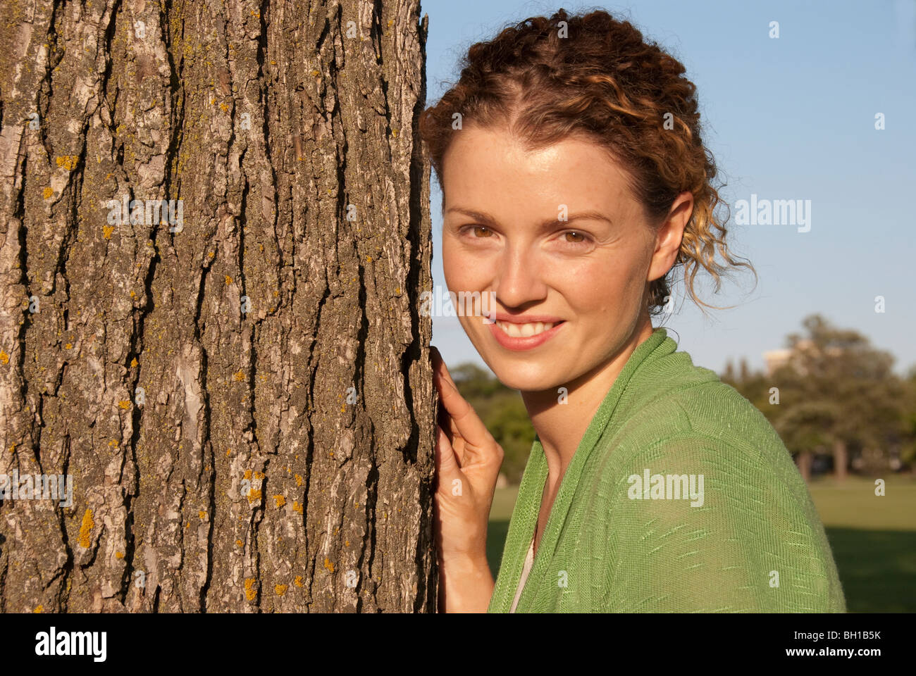 Mujer en sus 40's junto al árbol en Assiniboine Park, Winnipeg, Manitoba, Canadá Imagen De Stock