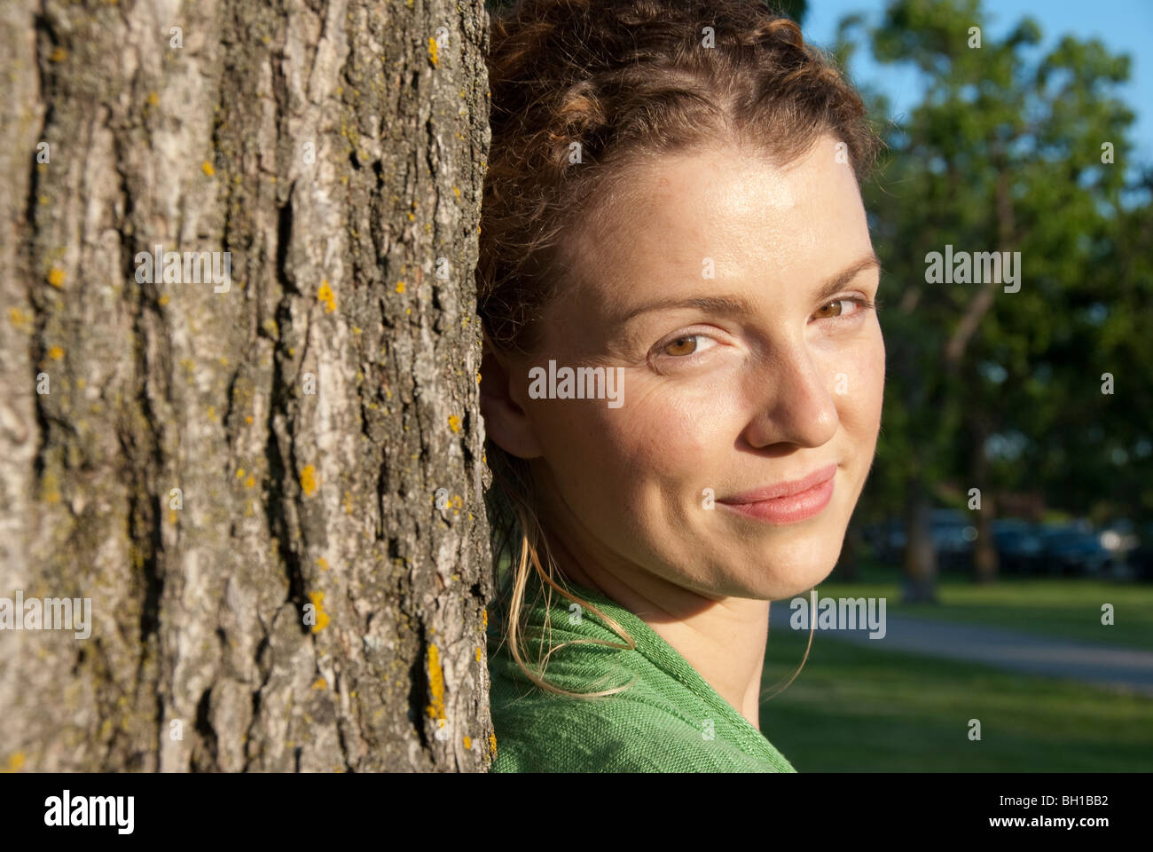 Retrato de mujer en sus 40s junto al árbol, Assiniboine Park, Winnipeg, Manitoba, Canadá Imagen De Stock