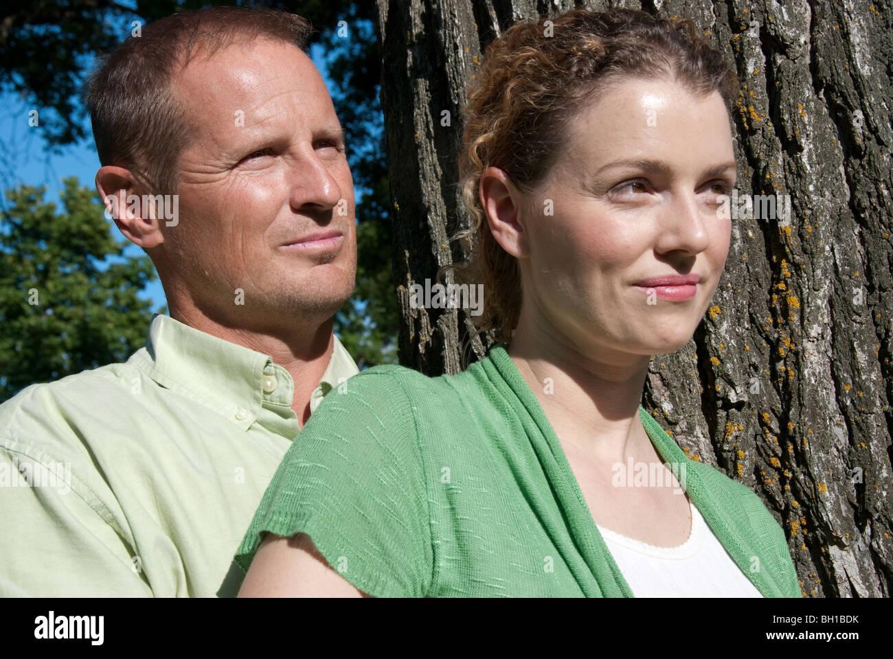 Retrato de pareja en sus 40s junto al árbol, Assiniboine Park, Winnipeg, Manitoba, Canadá Imagen De Stock