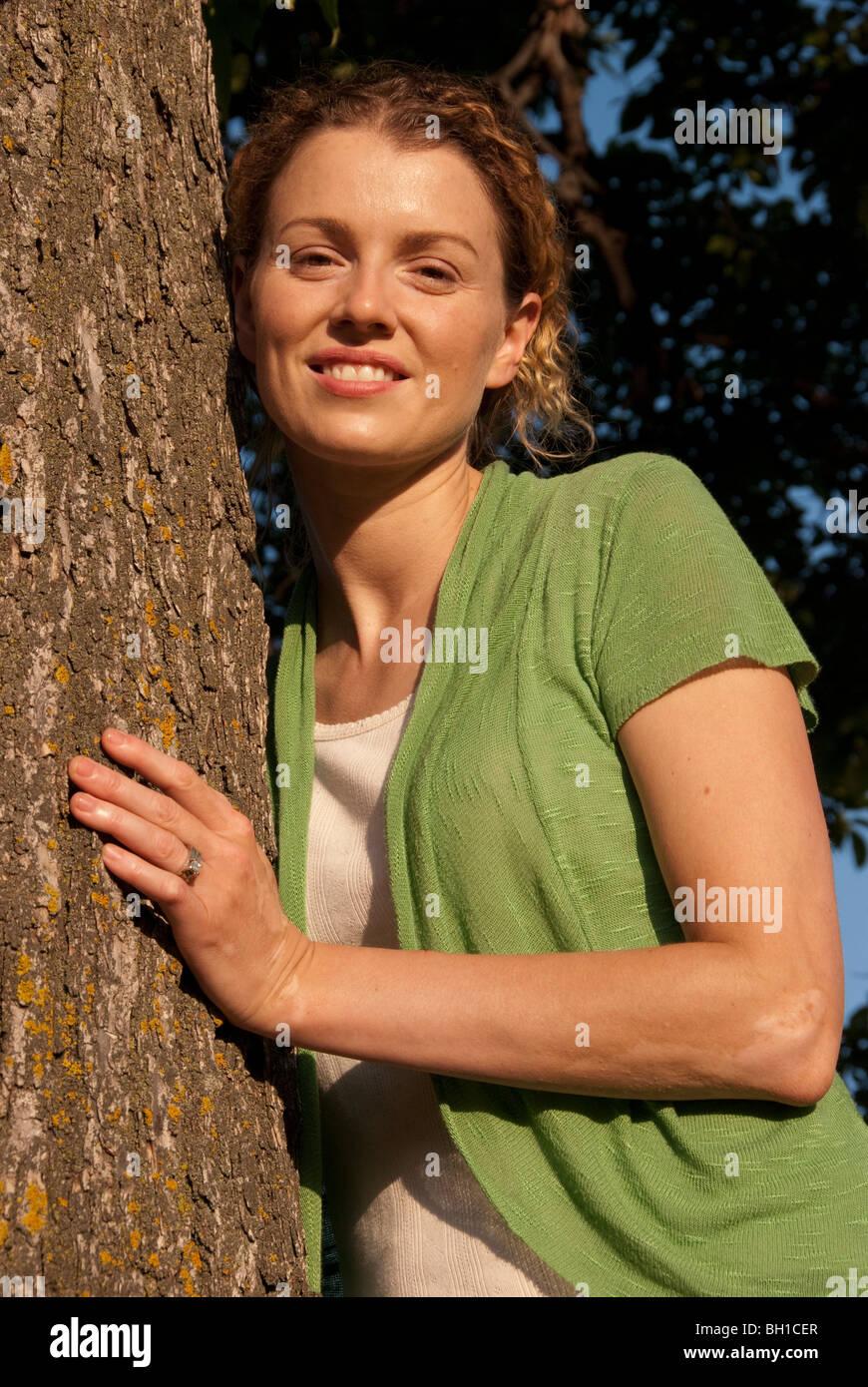 Mujer en sus 40's se recuesta contra el árbol en Assiniboine Park, Winnipeg, Manitoba, Canadá Imagen De Stock
