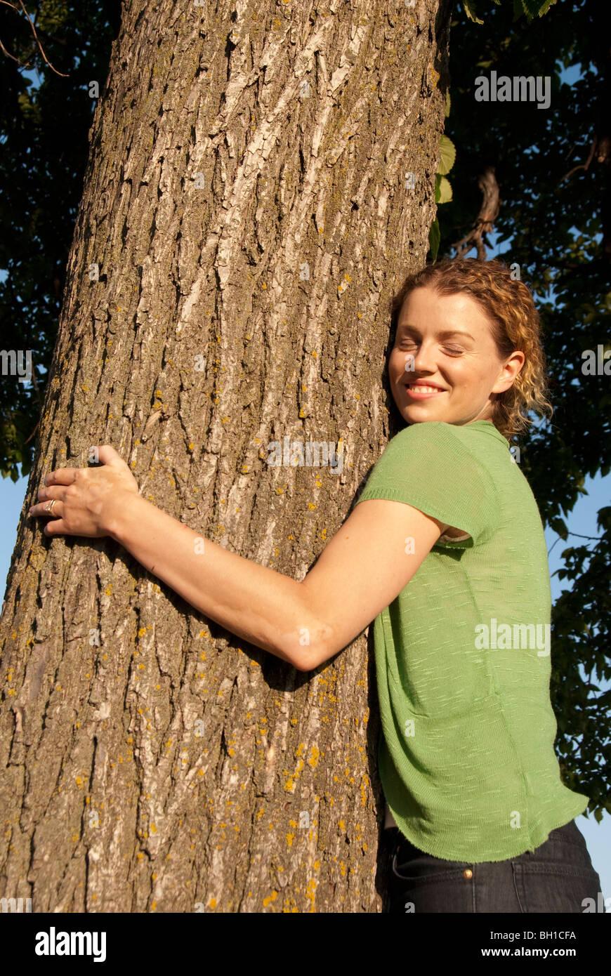 Mujer en sus 40's abrazos árbol en Assiniboine Park, Winnipeg, Manitoba, Canadá Imagen De Stock